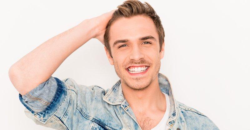 Man smiling with a full head of blonde hair transplant hair wearing denim top