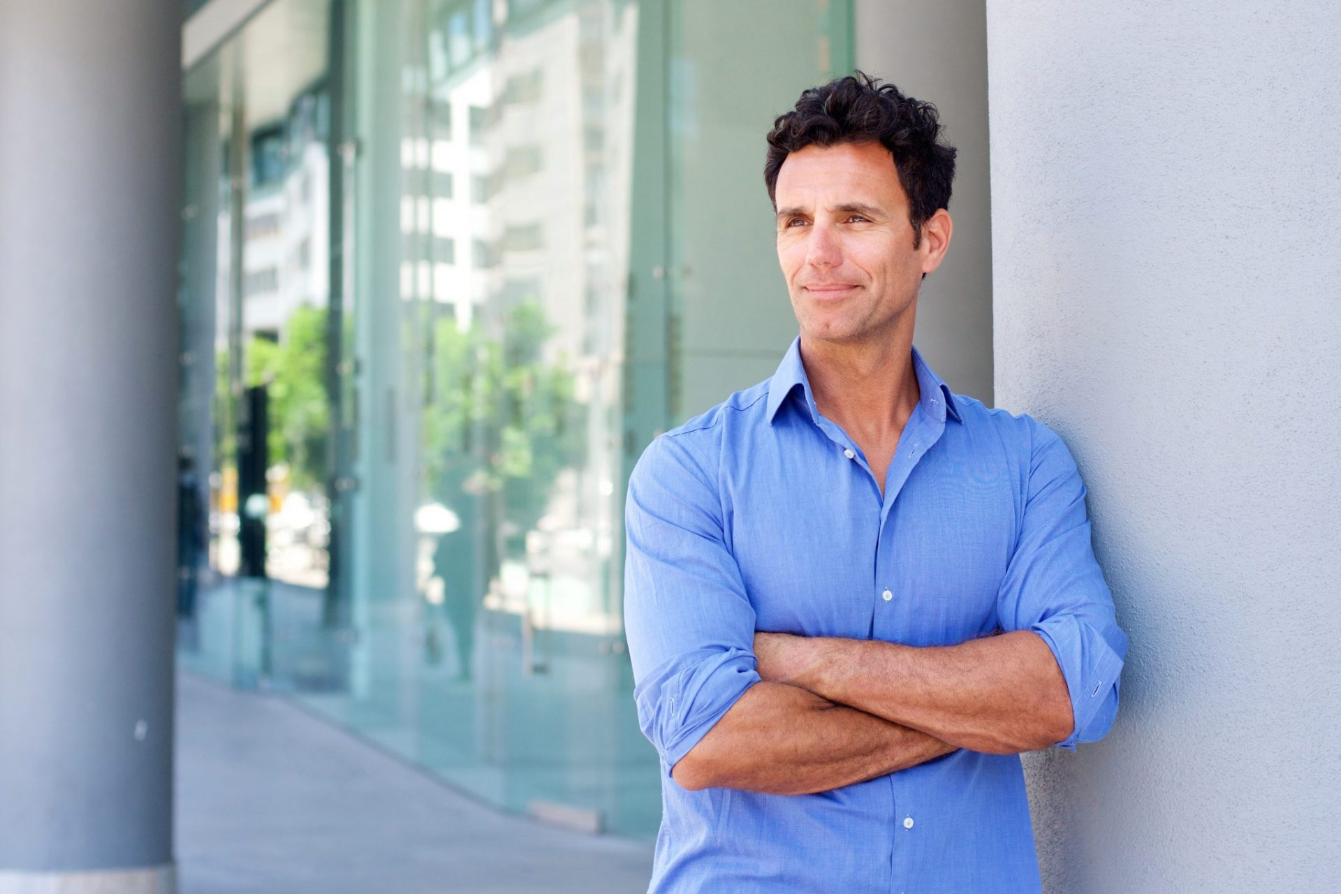 Portrait of a business man with nice hair standing outside with arms crossed