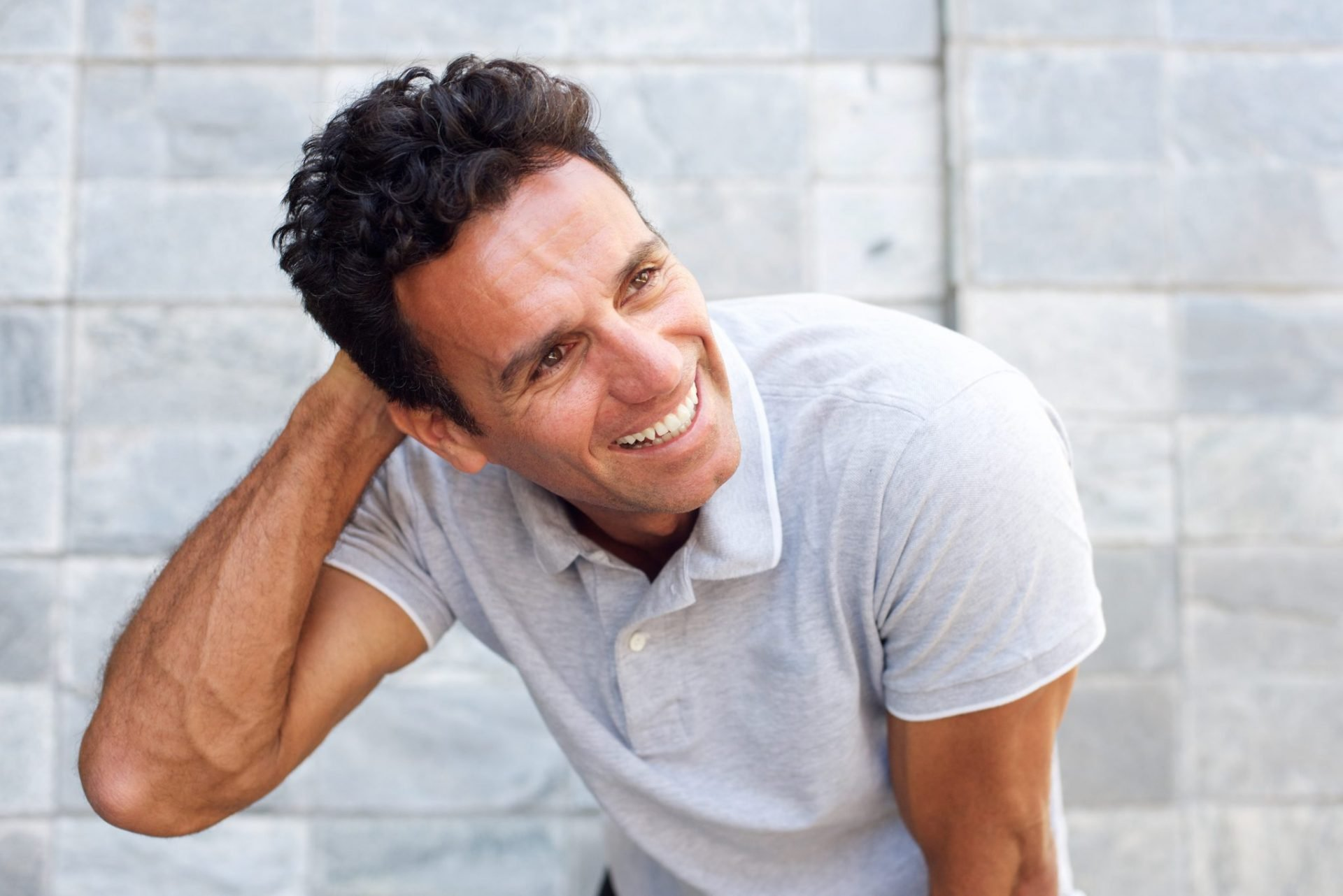 close up portrait of a handsome older man laughing with a black hair transplant.